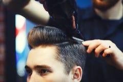 Le coiffeur masculin fait dénommer de cheveux d'un jeune homme à l'aide d'un dessiccateur images stock