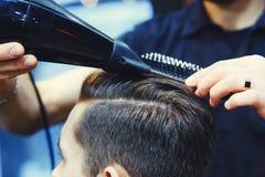 Le coiffeur masculin fait dénommer de cheveux d'un jeune homme à l'aide d'un dessiccateur photographie stock libre de droits