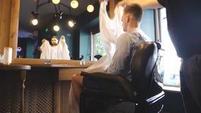 Le coiffeur masculin a fini pour exécuter une coupe de cheveux et enlever le cap de salon de son client au salon Le jeune coiffeu banque de vidéos