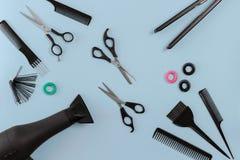 Le coiffeur a placé avec de divers accessoires sur le fond bleu Photos libres de droits