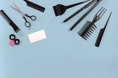 Le coiffeur a placé avec de divers accessoires sur le fond bleu Images libres de droits