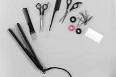 Le coiffeur a placé avec de divers accessoires sur le fond gris Photo libre de droits