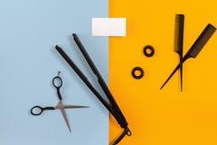 Le coiffeur a placé avec de divers accessoires sur le fond orange et bleu Photo libre de droits