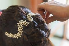 Le coiffeur prend une coiffure du ` s de jeune mariée son jour du mariage images stock