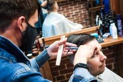 Le coiffeur principal coupe un homme dans le salon images libres de droits