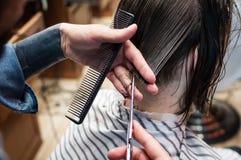 Le coiffeur principal coupe un homme dans le salon image libre de droits