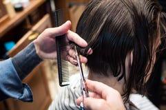 Le coiffeur principal coupe un homme dans le salon photographie stock libre de droits