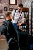 Le coiffeur principal professionnel coupe la barbe de client Photos stock
