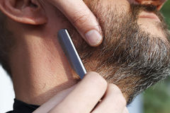 Le coiffeur principal tond l'homme de barbe photographie stock