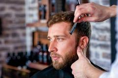 Le coiffeur rase la barbe du ` s d'homme avec une lame Photo stock