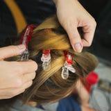 Le coiffeur roule des clients de cheveux avant teint photos stock