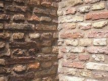 Le coin approximatif médiéval de mur de briques de la terre et de la terre cuite a coloré des briques Photo stock