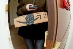 Le colis de balayage de femme de la livraison de colis d'UPS d'Amazone en ligne rouissent Photo libre de droits