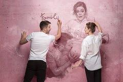 Le collage au sujet de l'écriture de couples quelque chose sur un mur rose Photos libres de droits