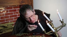 Le collecteur regarde sa richesse avec les bougies allumées banque de vidéos