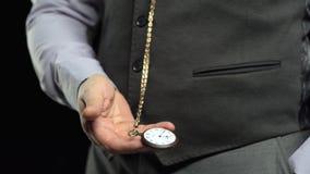 Le collecteur retire une montre sur une chaîne et met le temps dans sa paume Fond noir Son banque de vidéos
