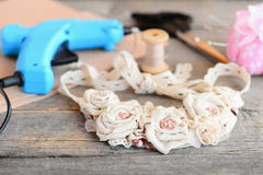 Le collier de tissu, collent l'arme à feu chaude, ciseaux, fil, l'aiguille, feutre sur une vieille table en bois Accessoire éléga Photo stock