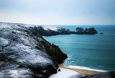 Le colline e l'acquamarina innevati, le acque cristalline di Porthcurno tirano in Cornovaglia, Inghilterra Immagine Stock