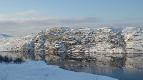 Le colline sono coperte di neve riflessa nel lago Fotografia Stock