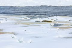 Le collinette e le banchise galleggianti sul fiume di inverno fotografie stock