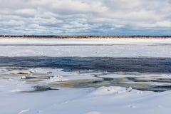 Le collinette e le banchise galleggianti sul fiume di inverno immagine stock