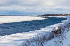 Le collinette e le banchise galleggianti sul fiume di inverno immagini stock libere da diritti