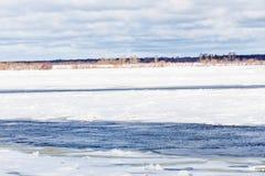 Le collinette e le banchise galleggianti sul fiume di inverno fotografia stock libera da diritti