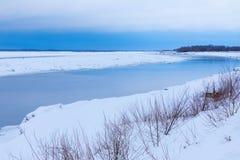 Le collinette e le banchise galleggianti sul fiume di inverno immagine stock libera da diritti