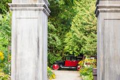 Le colonne di pietra nascoste oggetto d'antiquariato rosso dell'automobile del oltimer incorniciano l'albero immagini stock libere da diritti