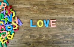 Le ` coloré d'AMOUR de ` de mot à côté d'une pile d'autres lettres Photos stock