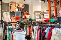 Le ` coloré s de femmes s'habille sur des cintres dans un magasin de détail Concept de mode et d'achats image stock