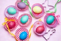 Le colorfur de Pâques eggs avec le ruban et cintre sur le fond rose Image libre de droits