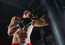 Le combattant des battements mélangés d'arts martiaux sur le sac avec son elbo photos libres de droits