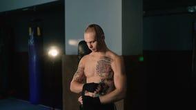 Le combattant gratuit enveloppe ses mains avec l'enveloppe de main noire avant la formation de combat 4K banque de vidéos
