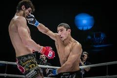 Le combattant mélangé d'arts martiaux obtient la main de coup à la tête de son adversaire photographie stock
