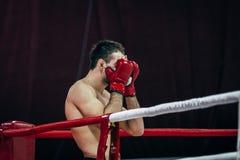 Le combattant masculin des arts martiaux mélangés a couvert son visage de mains dans les gants avant combat Photos libres de droits
