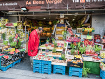 Le commerçant de Paris examine ses légumes au stand de fruit Photo libre de droits