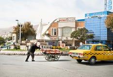 Le commerçant de tapis pousse un chariot avec des tapis sur une rue passante Photographie stock libre de droits
