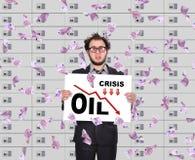 Le commerçant tenant l'affiche avec des statistiques tombent dans des prix du pétrole Photographie stock libre de droits