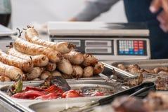 Le commerce a fait frire sur un gril, des saucisses et des légumes Photos libres de droits