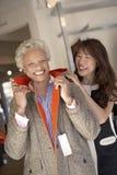 Le commis aidant la femme aînée essayent la jupe photographie stock libre de droits