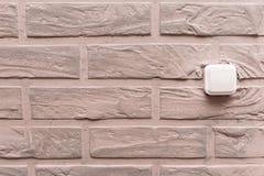 Le commutateur électrique en plastique est situé sur le mur, décoré du plâtre décoratif beige sous forme de briques dans l'intéri images stock