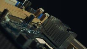 Le componenti della scheda madre stanno filando su un fondo nero, sulle scanalature di sata e su RAM, dispositivo di raffreddamen video d archivio