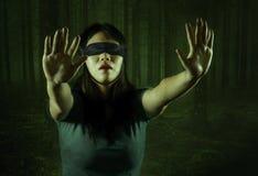 Le composé dramatique du jeune adolescent coréen asiatique effrayé et bandé les yeux que la fille a perdu dans la forêt foncée a  image libre de droits