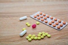 Le compresse e le capsule sono bolla sulla tavola Tabl multicolore Fotografia Stock