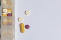 Le compresse e le pillole sono sparse fuori in un contenitore per le compresse i giorni della settimana Fotografie Stock Libere da Diritti
