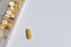 Le compresse e le pillole sono sparse fuori in un contenitore per le compresse i giorni della settimana Immagine Stock
