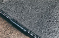 Le comprimé dans un cas en cuir sur une surface en bois Photo traitée Photos libres de droits
