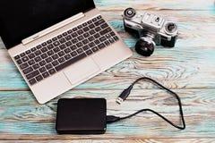 Le comprimé et l'appareil-photo se trouvant sur le fond bleu en bois Photographie stock