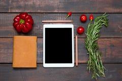 Le comprimé, le carnet, le poivron amer et doux frais sur le fond en bois de table Images libres de droits